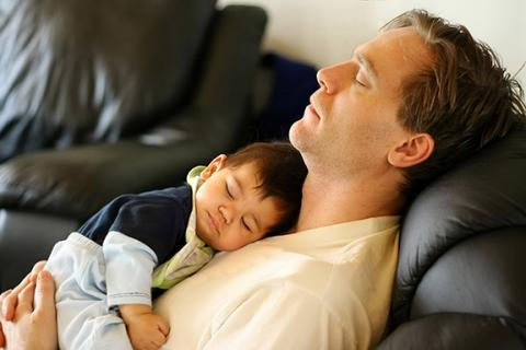 Man and baby sleeping on leather couch