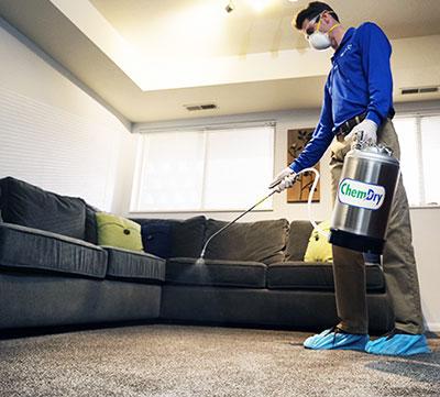 Chem-Dry techniction sanitising a wood floor